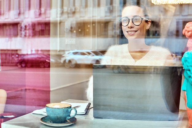 Attractive businesswoman in optical spectacles obile conversation with friend via smartphone device.positive young woman talking on telephone sitting at laptop computer in coffee shop