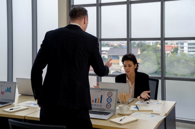 Attractive businesswoman and partner talking and discussing at meeting table with tablet computer presenting graphs, diagrams and charts of financial analysis on screen. business negotiation.