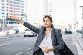 Attractive businesswoman raising her hand to call cab on city road