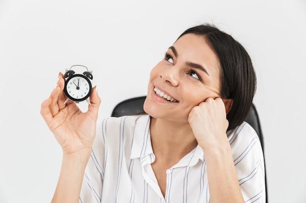魅力的な女性実業家は、オフィスの肘掛け椅子に座って、白い壁に隔離された小さな目覚まし時計を保持しながら喜んでいます
