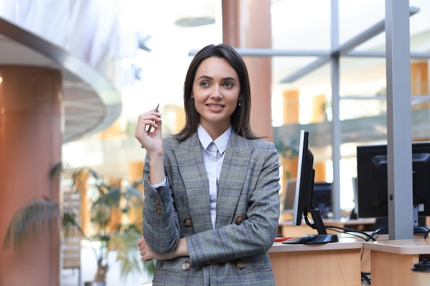 Attractive businesswoman standing near desk in the office and thinking abour new business concept.