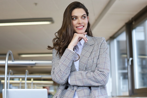 Attractive businesswoman standing near desk in the office.