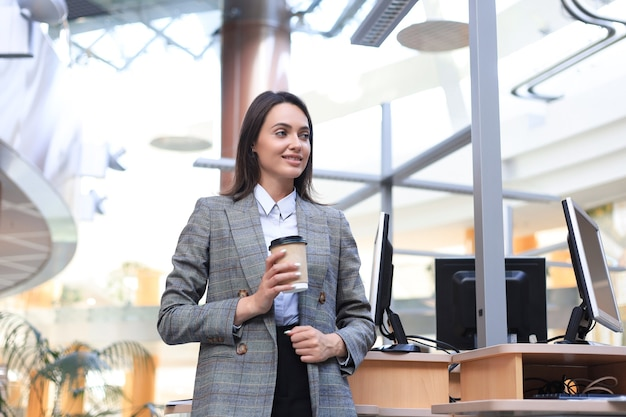 Attractive businesswoman standing with coffee near desk in the office.