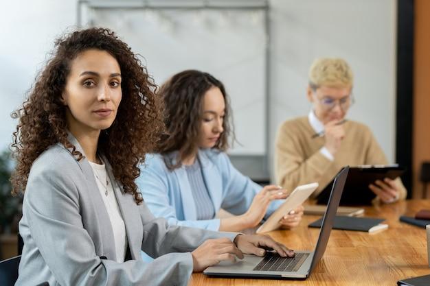 Привлекательная деловая женщина с ноутбуком, сидя за столом среди коллег