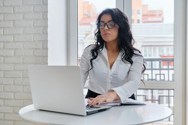 窓の近くの机に座って、コンピューターのラップトップで作業する魅力的な実業家