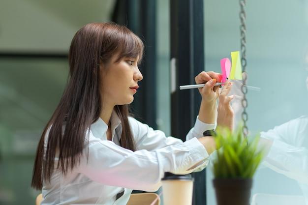 유리창 공유 아이디어에 스티커 메모에 그녀의 아이디어를 쓰는 매력적인 사업가