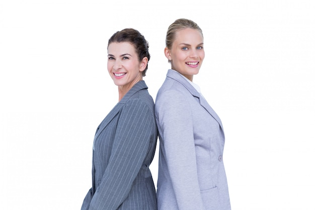 Attractive businesswomen standing back-to-back