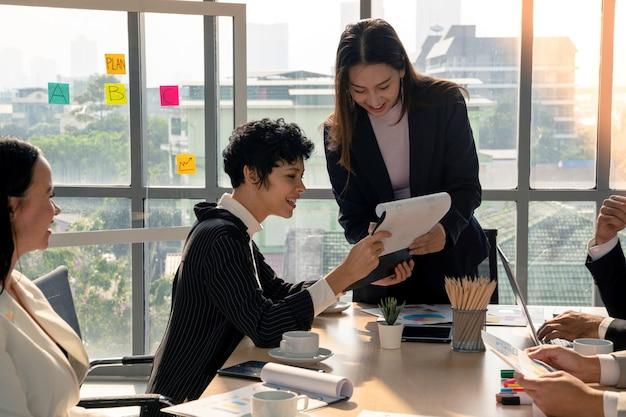 Привлекательная бизнес-леди консультируется с анализом из отчета финансового документа с позитивным настроением с руководителем группы во время встречи с разнообразными деловыми людьми в современном офисе, концепция лидерства женщины