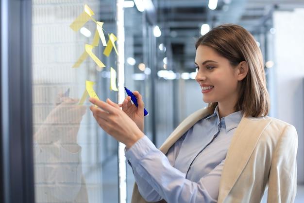 Привлекательная деловая женщина размещает наклейки на стекле в офисе и пишет на них.