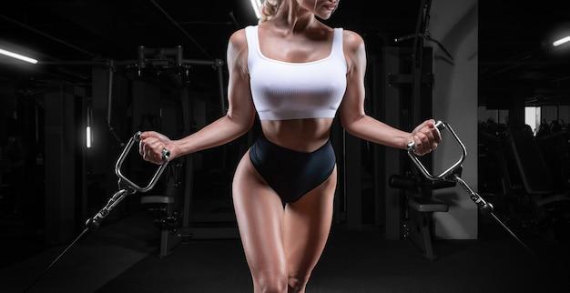 Привлекательная грудастая девушка тренируется в кроссовере. концепция фитнеса и бодибилдинга. смешанная техника