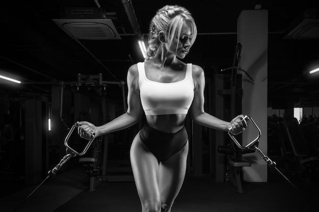クロスオーバーで運動する魅力的な巨乳の女の子。フィットネスとボディービルのコンセプト。