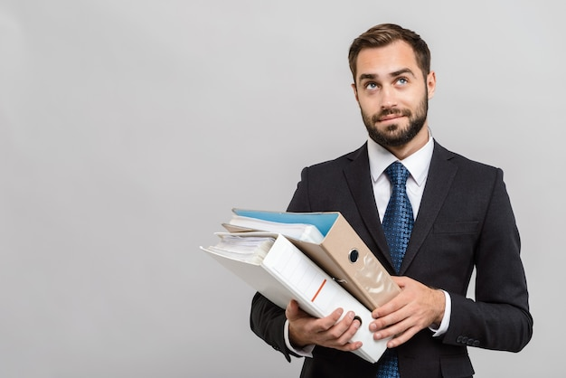 Привлекательный занятый молодой бизнесмен в костюме, стоящий изолированно над серой стеной, держа папки