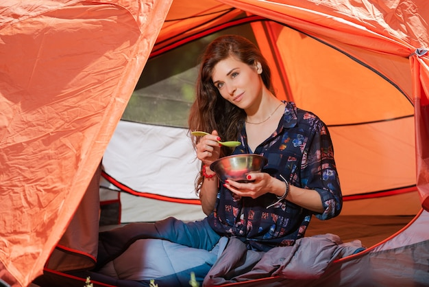 Attractive camper girl with plate and spoon