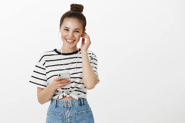 Привлекательная беззаботная девушка улыбается, надевает наушники, чтобы слушать подкаст или музыку на мобильном телефоне