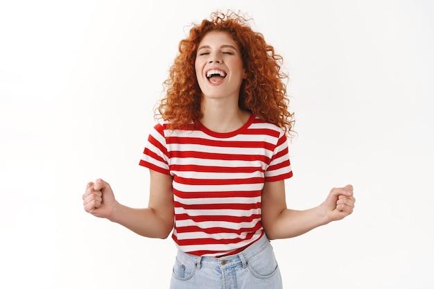魅力的なのんきな活気のある赤毛の巻き毛の女性は、目を閉じて踊る感情を解放する楽しみを楽しんでいますはいスリル満点のクランチ拳が当選した宝くじに勝ちます