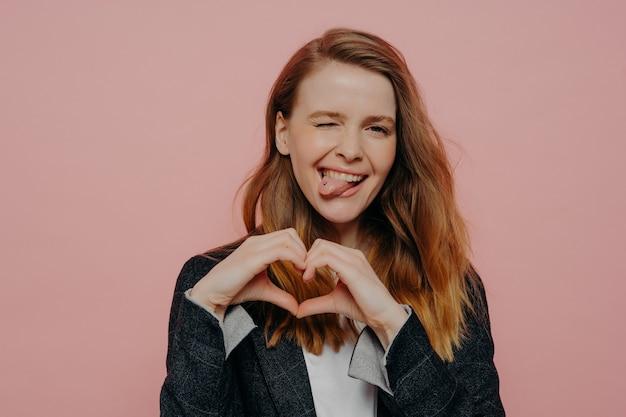 ハート型のサインを示すフォーマルなダークジャケットの波状の生姜髪の魅力的な屈託のない若い女性、スタジオで淡いピンクの壁に立ってウインクして舌を突き出し、楽しみを表現