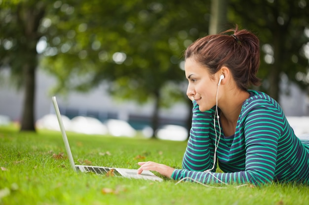 Attractive casual student lying on grass using laptop