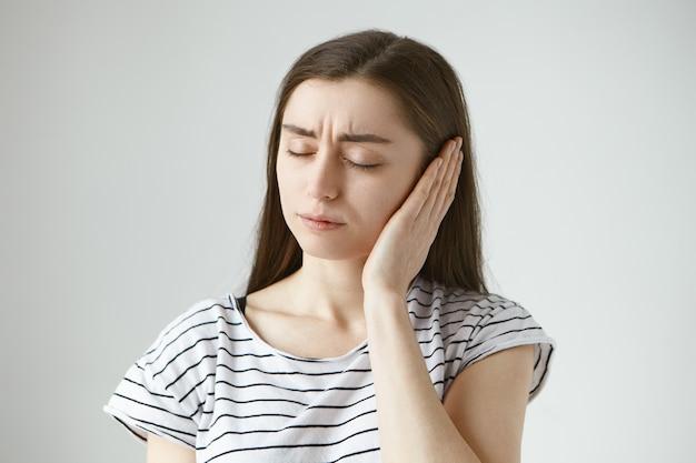 매력적인 캐주얼 옷을 입은 젊은 검은 머리 여성은 눈을 감고 청각에 문제가있는 동안 손으로 아픈 귀를 가리고 있습니다. 건강, 사람과 고통 개념
