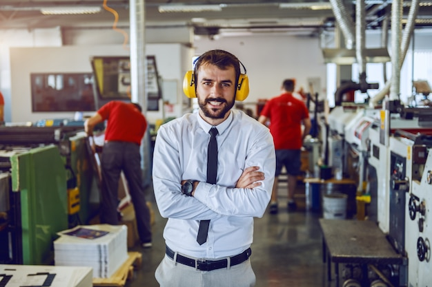 Attractive caucasian bearded director in shirt and tie and with antiphons on ears standing with arms crossed in printing shop.