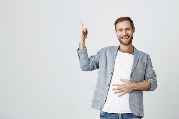 Attractive caucasian bearded guy in casual jacket pointing up