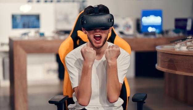 Привлекательный кавказский бородатый мужчина пробует технологию виртуальной реальности, сидя в кресле в магазине техники.