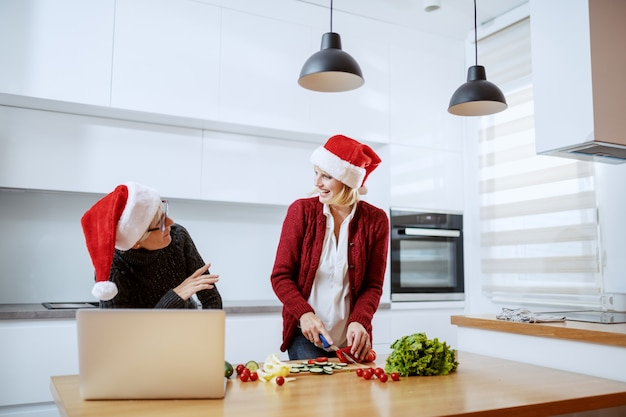 Attractive caucasian blonde woman chopping vegetables and preparing healthy christmas dinner. her mother standing next to her and giving her an advice how to cook. both have santa hats on heads.