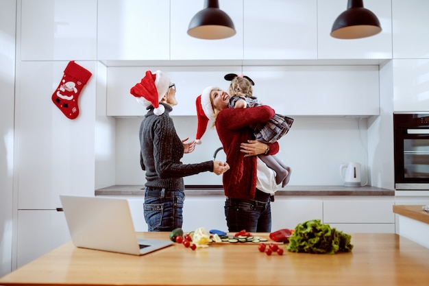 Attractive caucasian blonde woman with santa hat on head holding her little girl and hugging her. grandmother standing next to them and having santa hat on head, too. kitchen interior. christmastime.