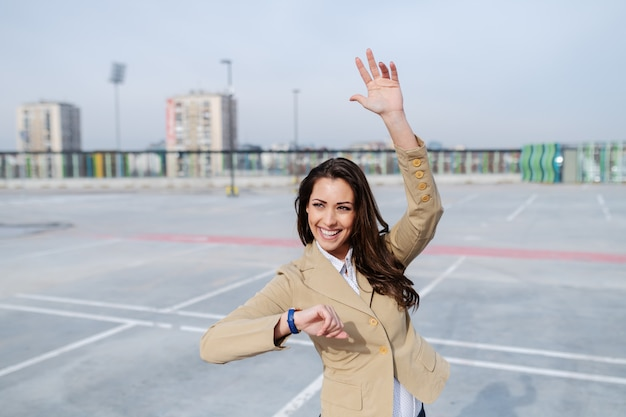 駐車場に立っているとタクシーの運転手に手を振っているベージュのジャケットに身を包んだ魅力的な白人ブルネット。