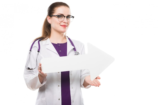 Attractive caucasian brunette female doctor standing in office smiling with paper arrow in her hands