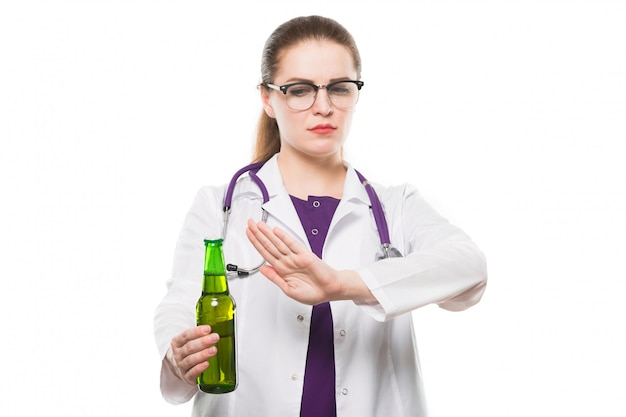 Attractive caucasian brunette female doctor standing in office with bottle of beer in her hands showing prevention sign on white