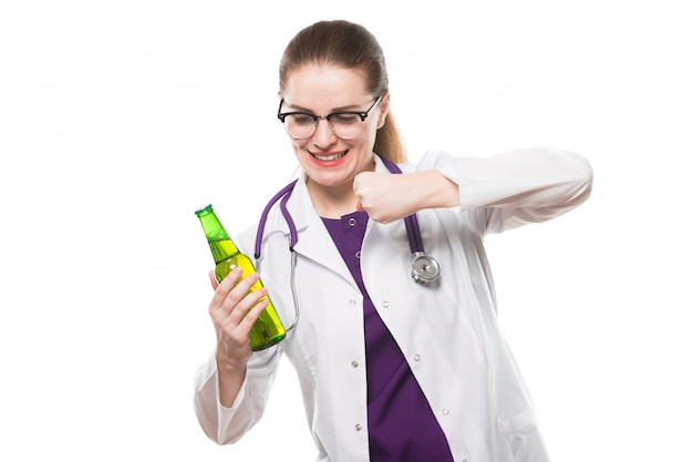 Attractive caucasian brunette female doctor standing in office with bottle of beer in her hands showing prevention sign