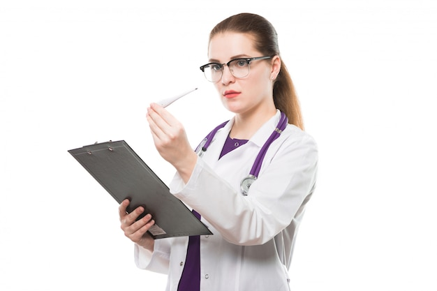 Attractive caucasian brunette female doctor standing in office with thermometer