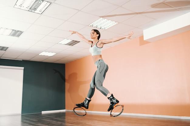 운동복과 kangoo에 매력적인 백인 갈색 체육관에서 점프 신발 점프.