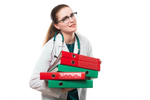 Attractive caucasian brunette sad female doctor standing in office with binders in her hands