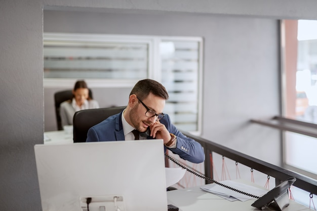 Attractive caucasian businessman in formal wear sitting at his work station and having a phone call while looking at paperwork. if you want to achieve greatness stop asking for permission.