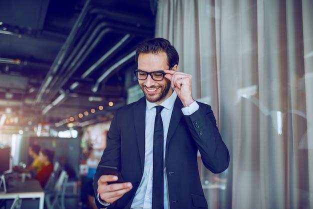 スーツと眼鏡が会社に立って、スマートフォンでメッセージを読んで魅力的な白人実業家。背景には、従業員が働いています。