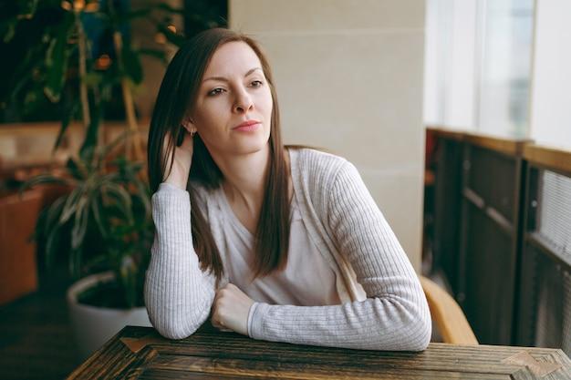 가벼운 캐주얼 옷을 입은 매력적인 백인 꿈꾸는 여성이 커피숍의 큰 창문 근처에 혼자 앉아 자유 시간에 레스토랑에서 휴식을 취합니다. 카페에서 휴식을 취하는 젊은 여성. 라이프 스타일 개념입니다.