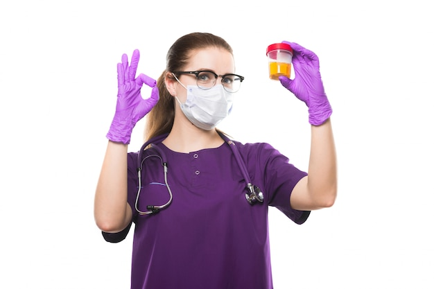 Attractive caucasian female doctor holding urine sample in her hands in medical mask and sterile gloves show ok sign on white