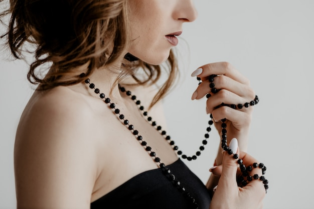 Attractive caucasian girl in a black dress twirled a string of beads around her fingers