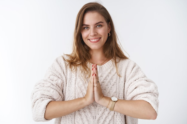 Attractive caucasian girl in loose sweater, hold hands in pray, smiling cheerful, thanking for help, appreciate, say namaste, begging for favor, stand white background