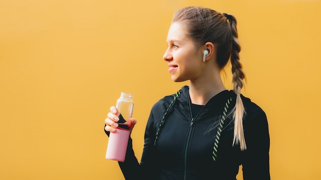 Attractive caucasian girl on yellow isolated background with wireless headphones in sport suit make workout, run and drinking water