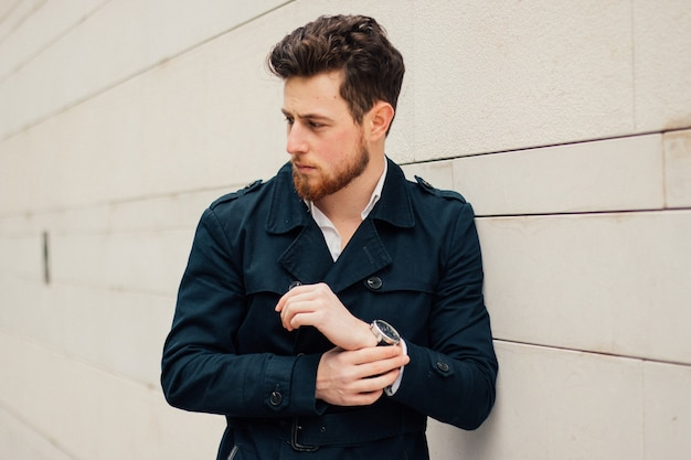 Attractive caucasian man in a blue coat posing near the wall