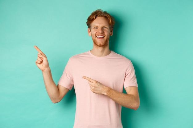 티셔츠를 입은 매력적인 백인 남자가 왼쪽으로 손가락을 가리키며 행복하게 웃고 광고를 보여주며 청록색 배경 위에 서 있다