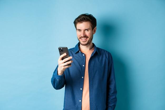 매력적인 백인 남자 휴대 전화를 사용 하여 행복 하 고 미소를 카메라, 파란색 배경에 서있는 찾고.