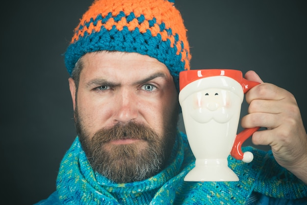 Привлекательный кавказский мужчина с бородой и усами в шляпе и шарфе с удовольствием выпил красивый бородатый