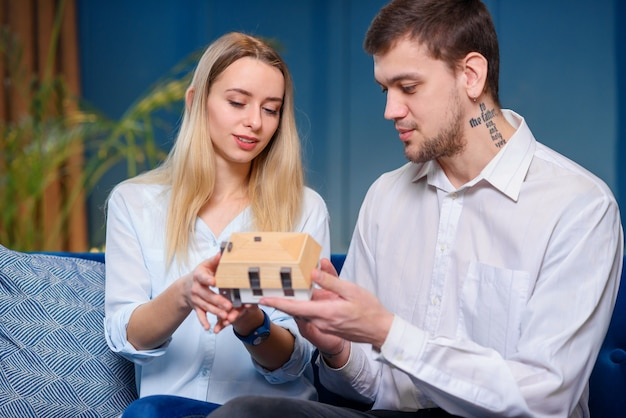 Attractive caucasian man and woman discussing design of the model of 3d maket of house.