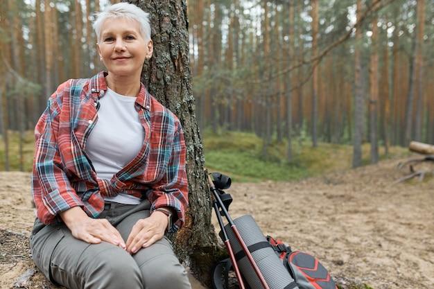 그녀의 옆에 배낭과 함께 나무 아래에서 휴식을 취하는 매력적인 백인 성숙한 여인, 웃고, 숲에서 하이킹하는 동안 숨을 쉬고, 야생의 자연의 평화와 평온을 즐기고