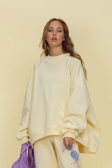 黄色の背景にポーズをとる黄色のスポーツウェアの魅力的な白人モデル