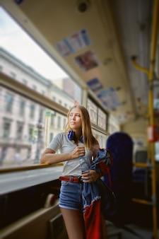 긴 금발 머리와 헤드폰을 가진 약 25 세의 매력적인 백인 잠겨있는 여성이 대중 교통에 서 있습니다.