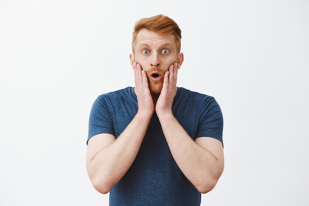 Attractive caucasian redhead man with bristle expressing surprised and amazement, touching face and folding lips, standing in stupor and popped eyes, being under impression